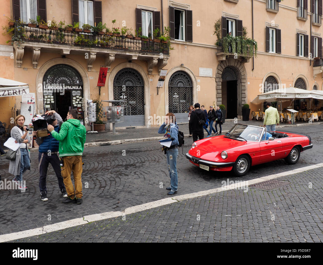 Film crew and male models in a classic Alfa Romeo sportscar on Piazza Navona in Rome, Italy - Stock Image