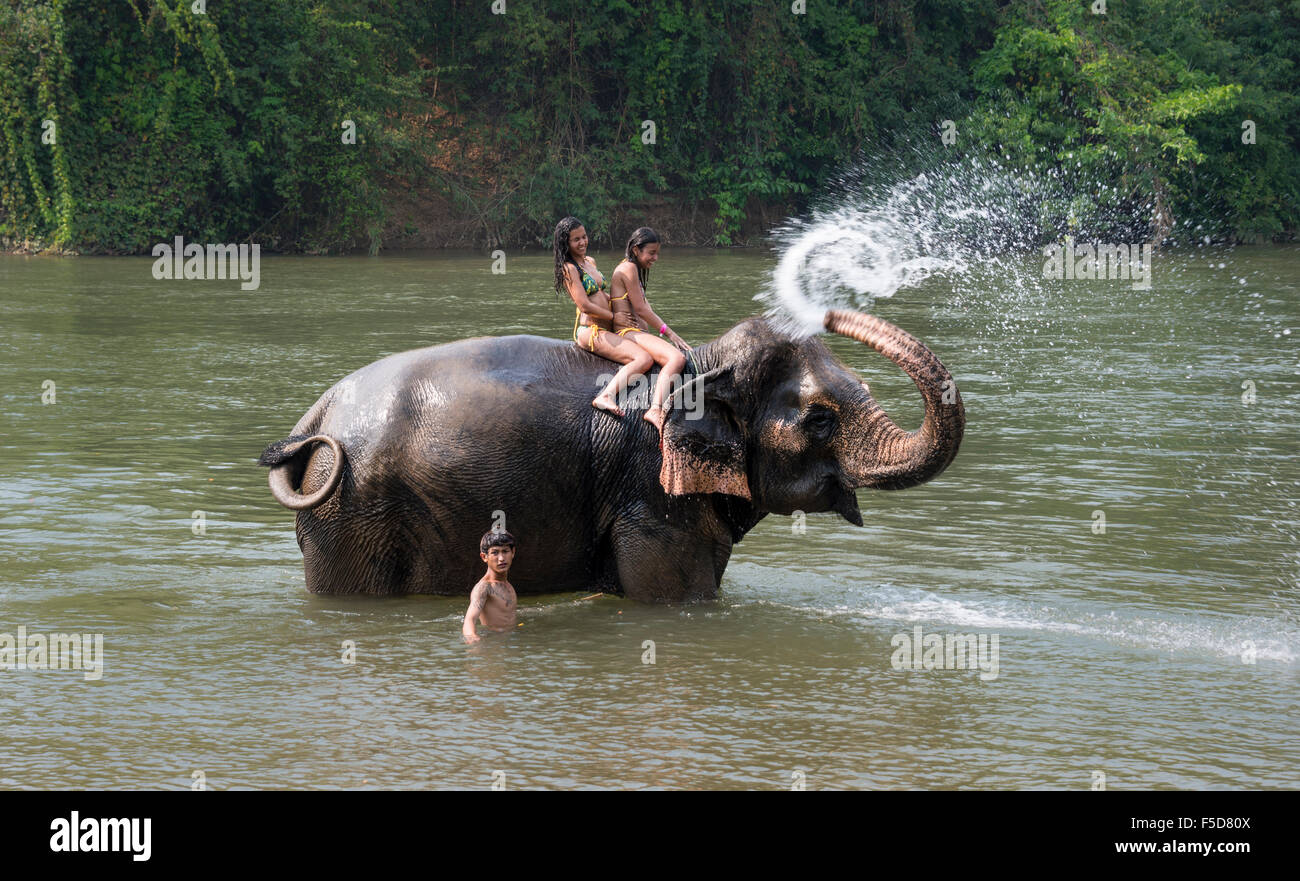 Elephant spraying two tourists, Kanchanaburi Province, Central Thailand, Thailand - Stock Image