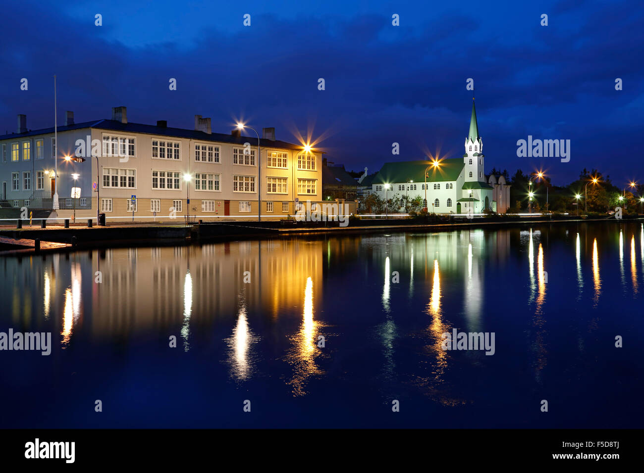 Buildings reflected on Tjorning Pond (Frikirjan Church on right), Reykjavik, Iceland - Stock Image