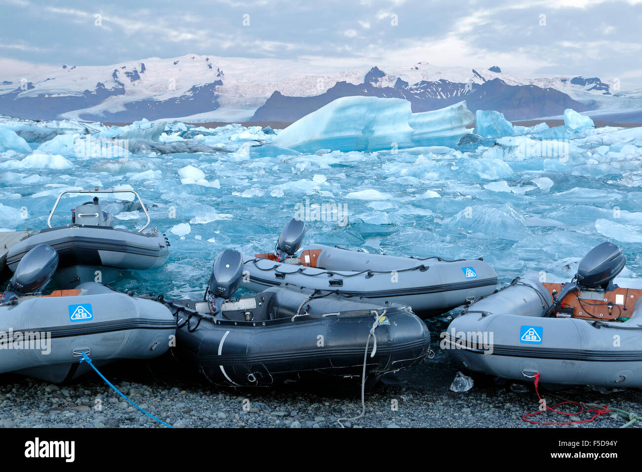Dinghies, icebergs and snow-covered mountains, Jokulsarlon Glacier Lagoon,  Vatnajokull National Park, Iceland - Stock Image