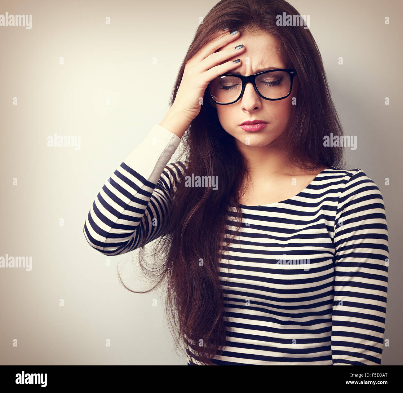 Beautiful business woman with headache holding head the hand with unhappy emotion. Vintage closeup portrait - Stock Image