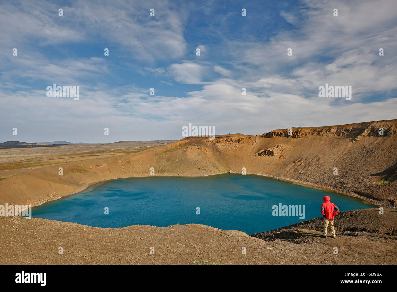 Hiker admiring explosion crater Viti, Krafla Volcano, near Reykjahlid, Iceland - Stock Image