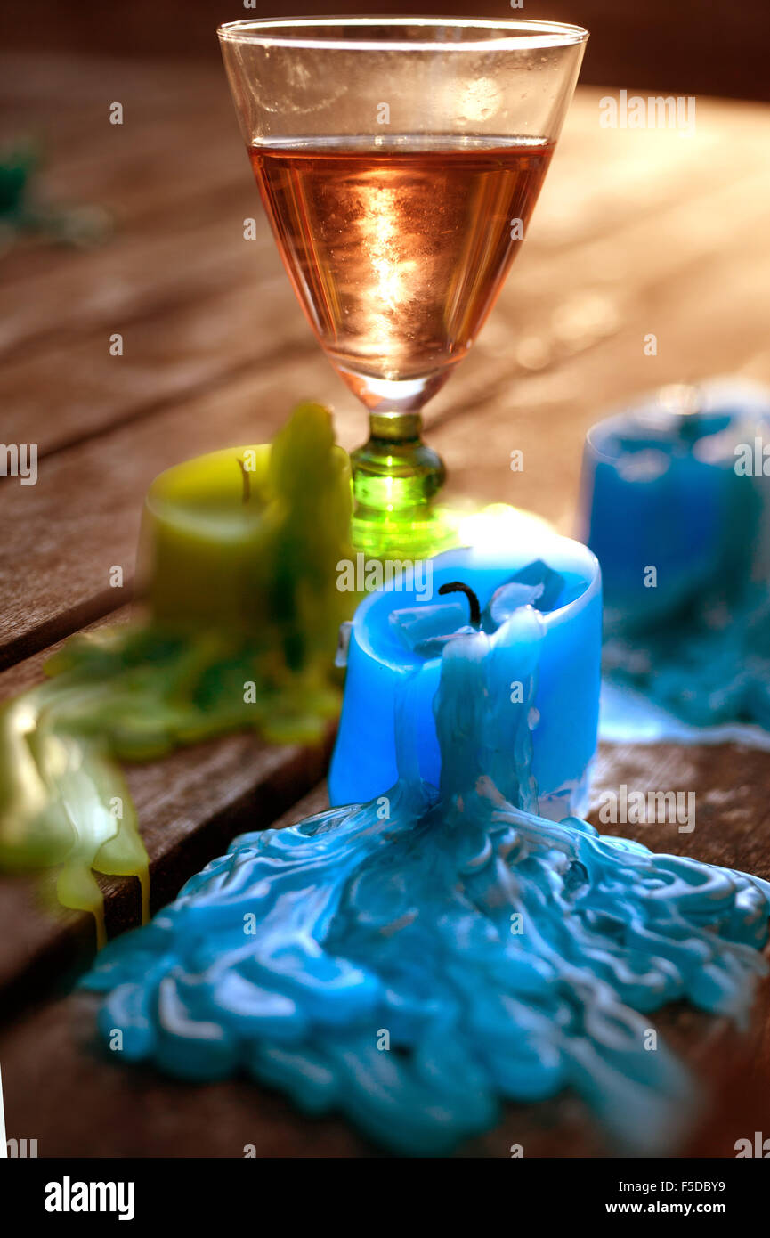 Glass of rose wine and melted candles after party - Stock Image