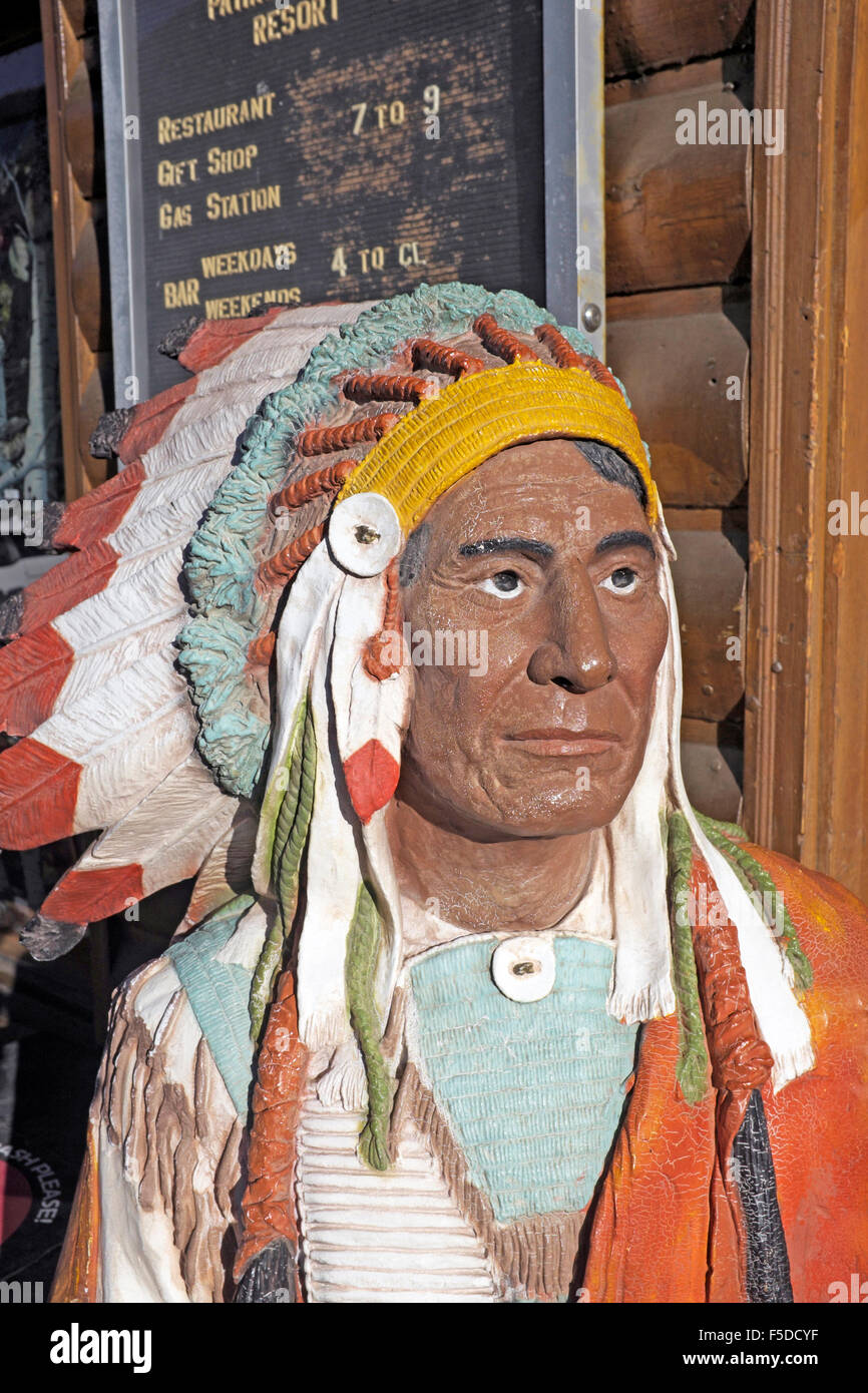 A hand-carved wooden indian at a gift shop and curio store at the eastern entrance of Yellowstone National Park - Stock Image