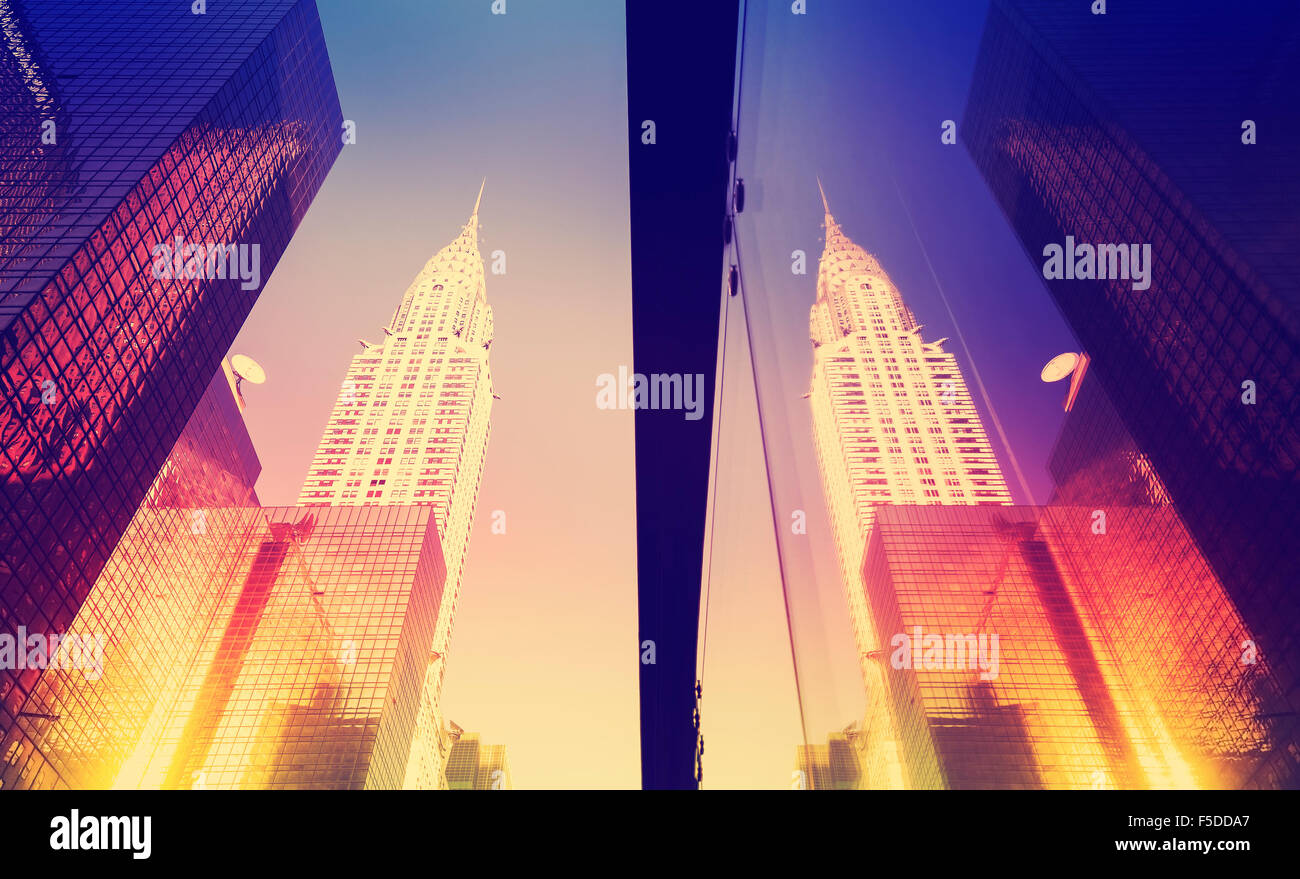 Vintage style Manhattan skyscrapers at sunset reflected in windows, NYC, USA. - Stock Image