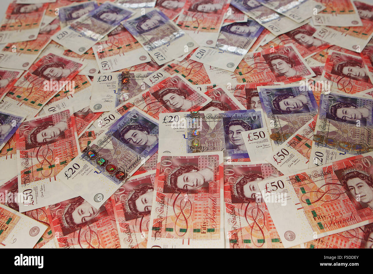 Pile of £20 and £50 notes scattered. - Stock Image