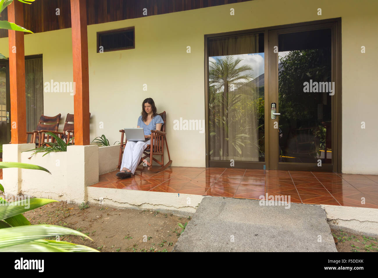 Woman sitting on the veranda and working on laptop - Stock Image