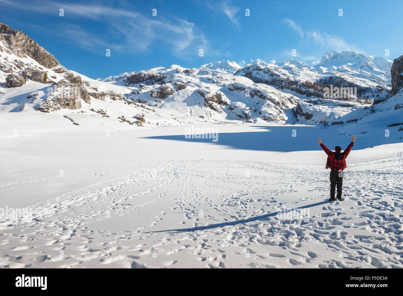 A young caucasian man by frozen Ercina Lake, Covadonga, Picos de Europa National Park, Asturias, Spain. - Stock Image