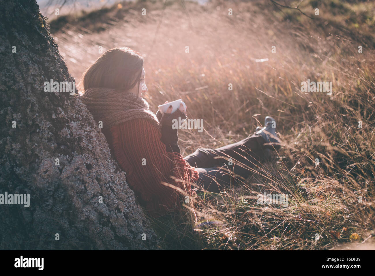 Woman in nature drinking tea or coffee. - Stock Image