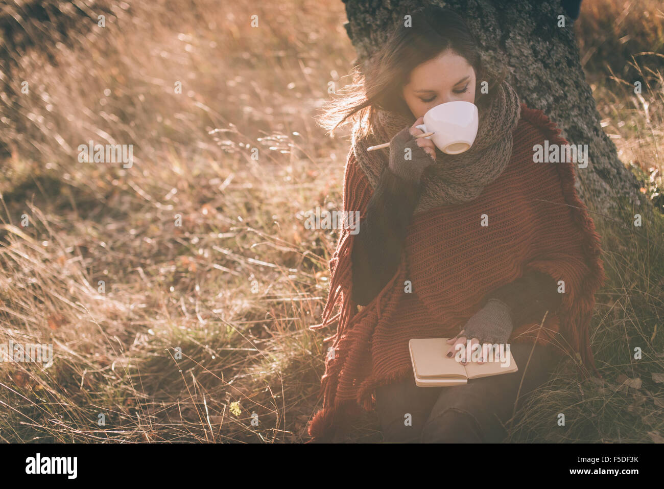 Woman in nature drinking tea or coffee. Writing in a notebook - Stock Image