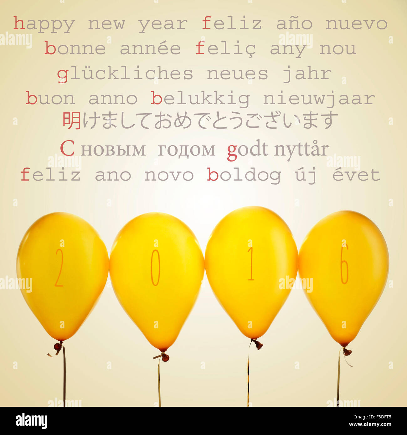 four golden balloons with the number 2016 and the text happy new year written in different languages, such as spanish, - Stock Image