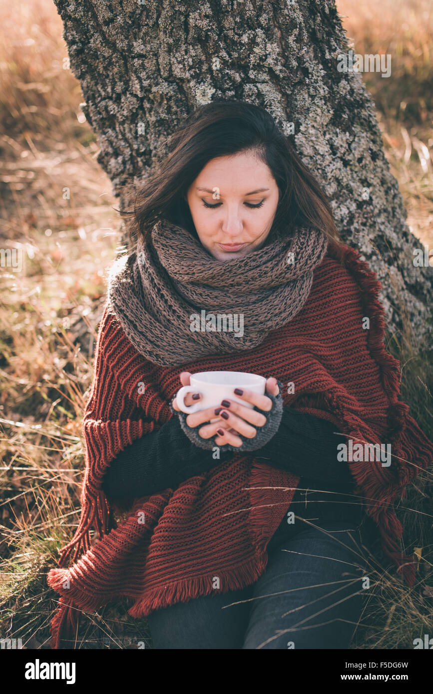 Woman in nature holding cup with tea or coffee - Stock Image
