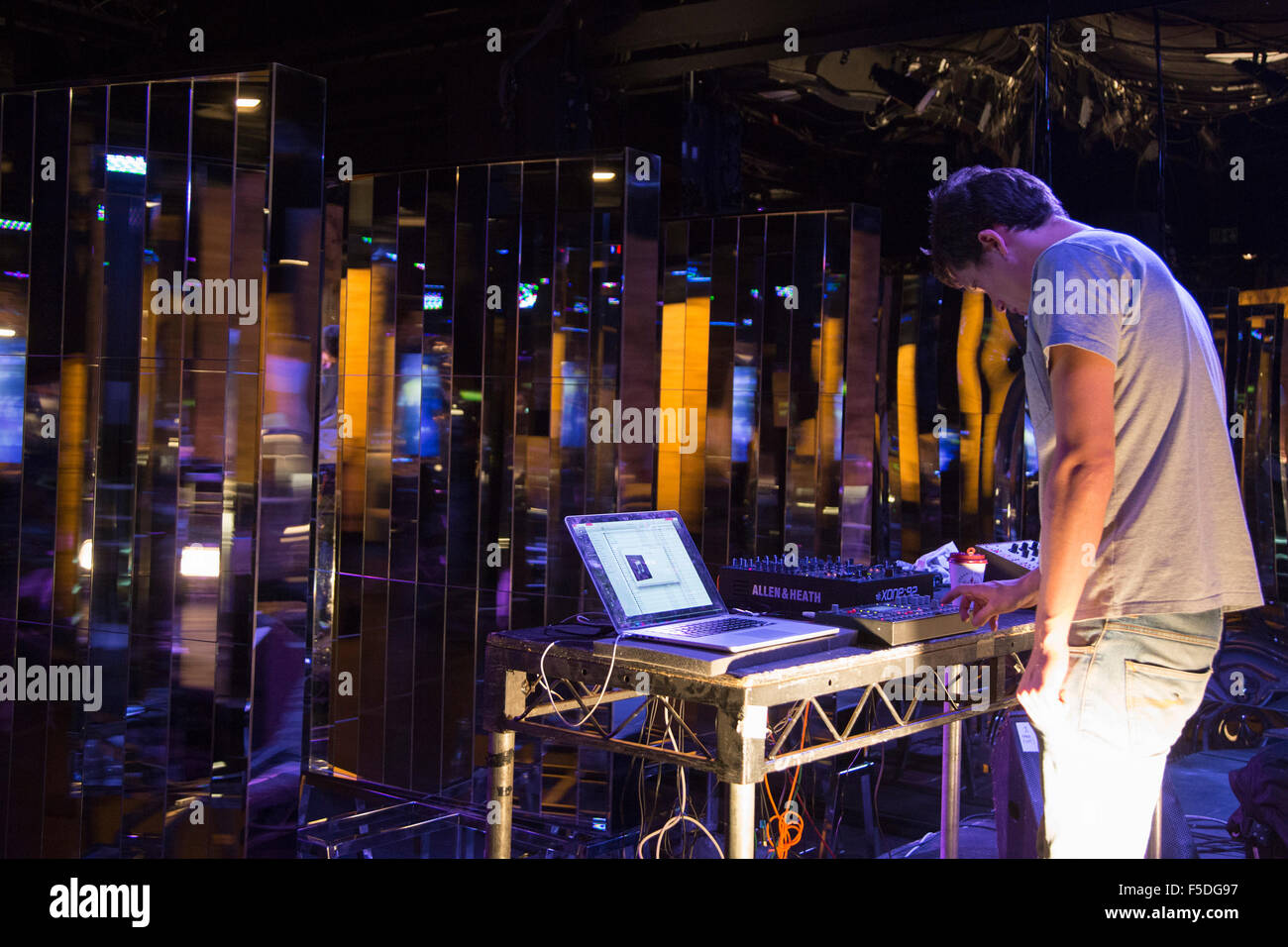 """DJ Powell performs on stage. The exhibition by Chinese artist Zhang Ding entitled """"Enter the Dragon"""", inspired by Stock Photo"""