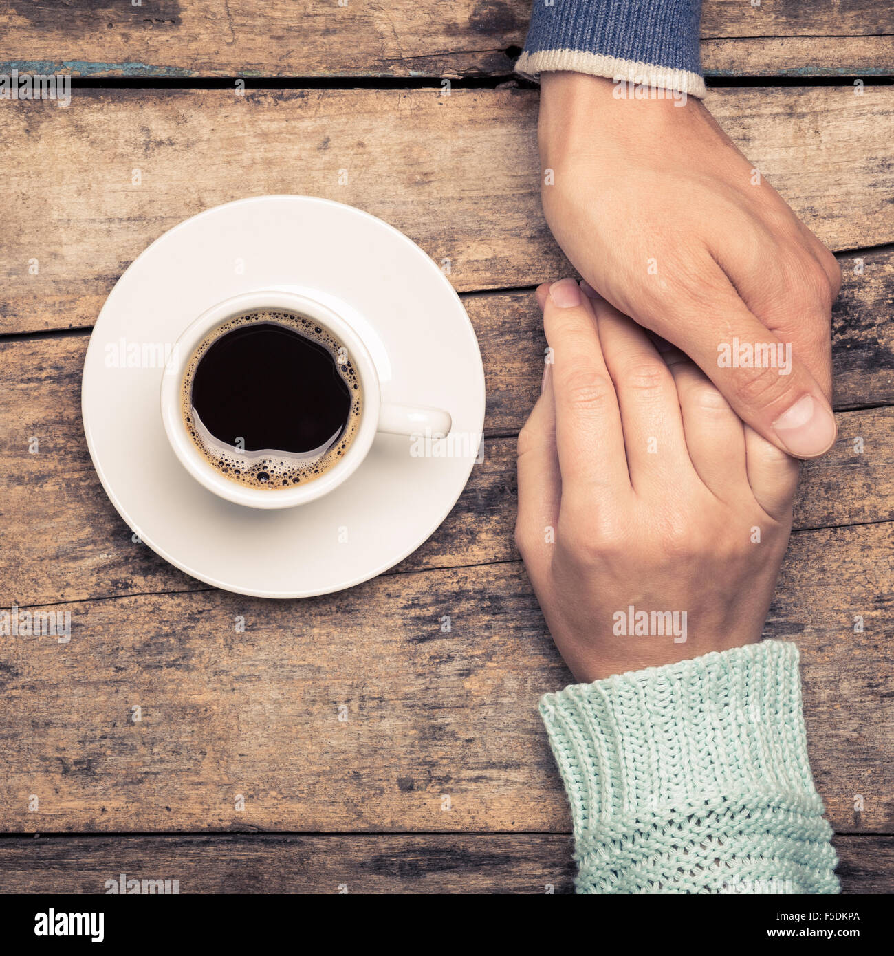 Close up image of people relations background. Man holding woman's hand near cup of coffee. Warm color toned - Stock Image