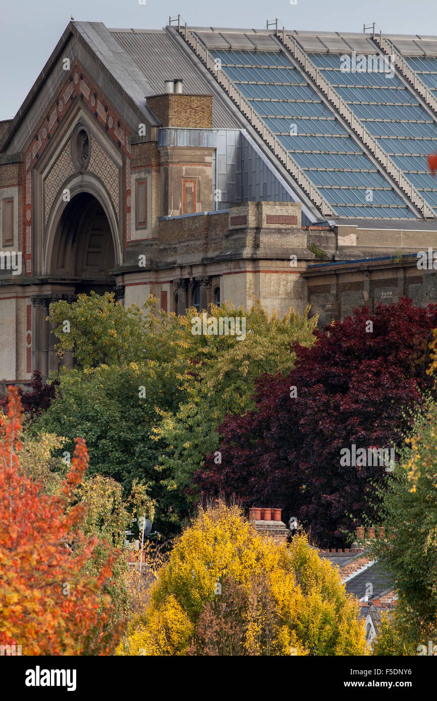 Alexandra Palace overlooks the trees and chimney pots of Dukes Avenue, a street in the North London district of - Stock Image