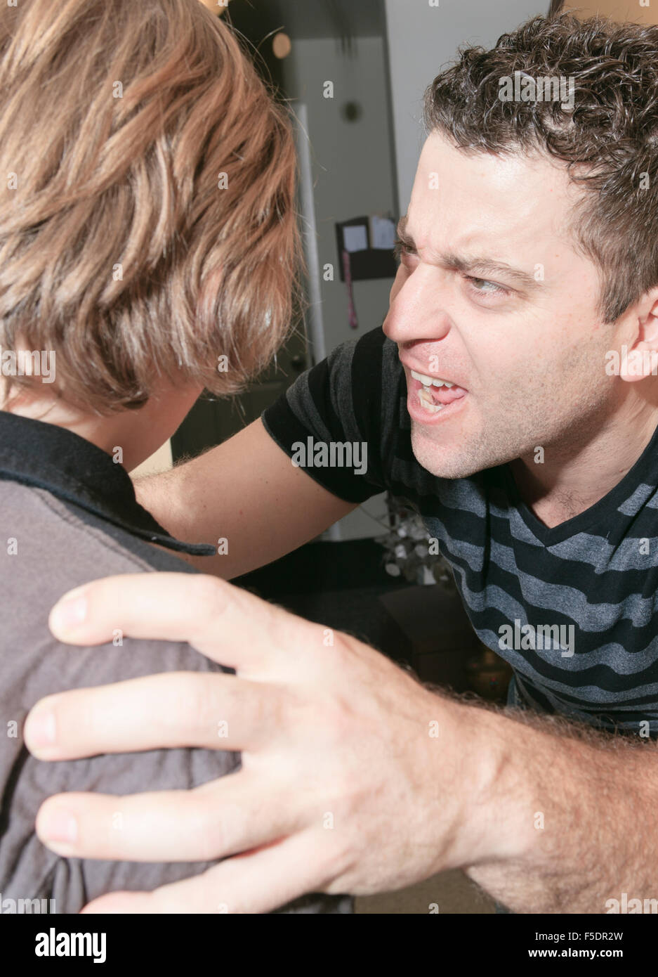 violent father hit the teenager of the family - Stock Image
