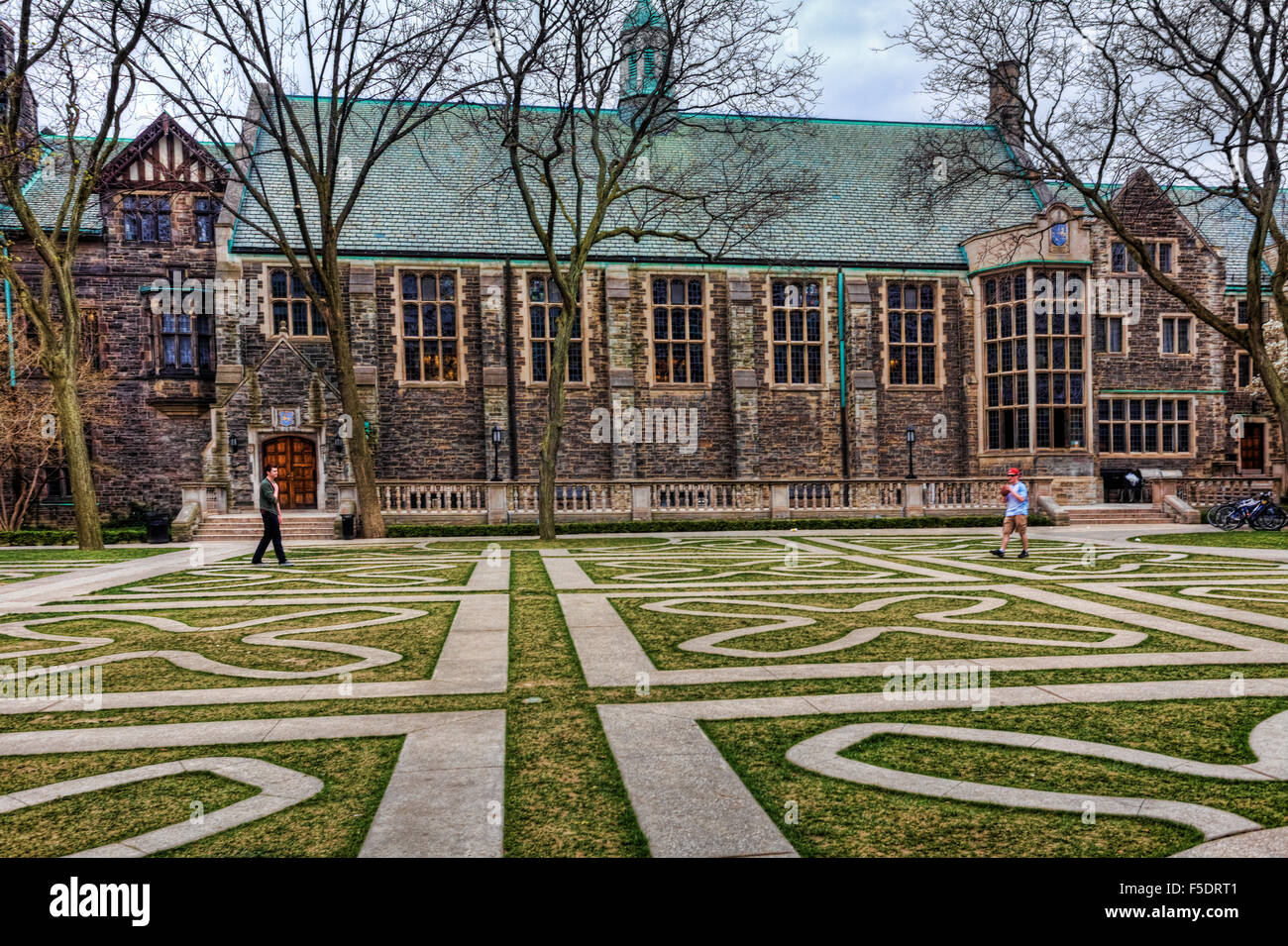 Two students play football in the commons area of Trinity College in Toronto - Stock Image