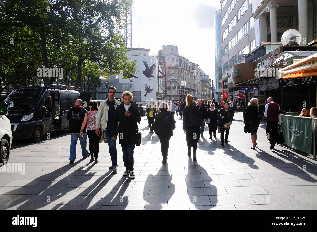 Pedestrians walking through Leicester Square, West End, City of Westminster, London, England, United Kingdom - Stock Image