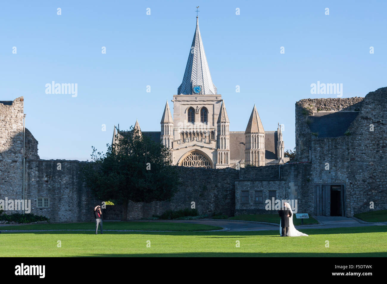 Wedding couple being photographed in grounds of Rochester Castle, Rochester, Kent, England, United Kingdom - Stock Image