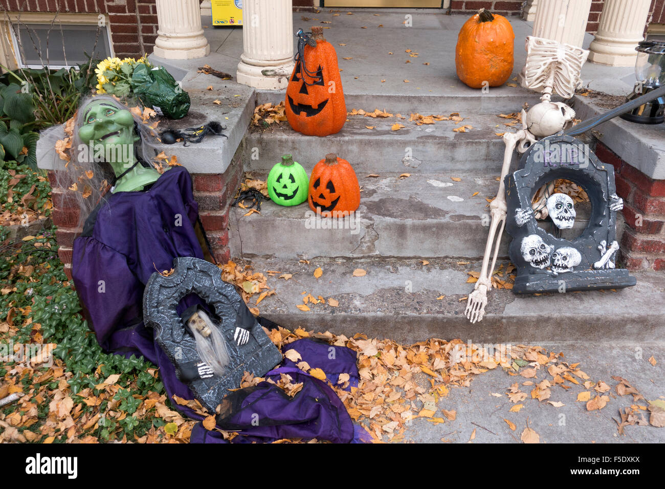 Halloween display of jack-o'-lanterns, skeletons and mummies on front steps of residential home. St Paul Minnesota - Stock Image