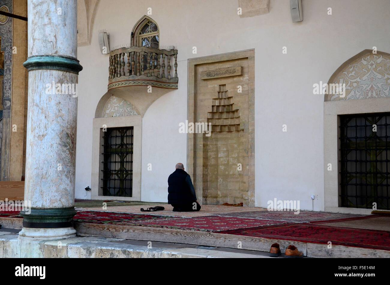 Lone Muslim man prays outdoors near mihrab and below balcony at Sarajevo mosque  Bosnia Hercegovina - Stock Image