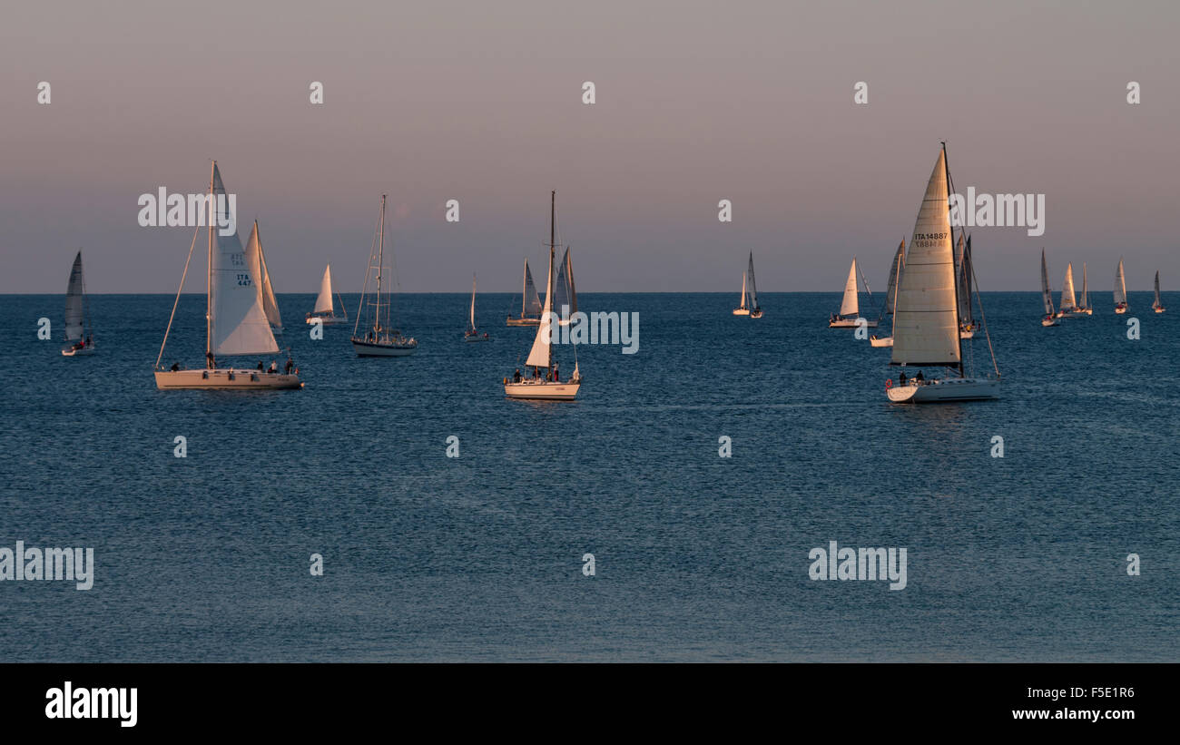 Many small sail boats cruising the Mediterranean Sea early in the morning. - Stock Image