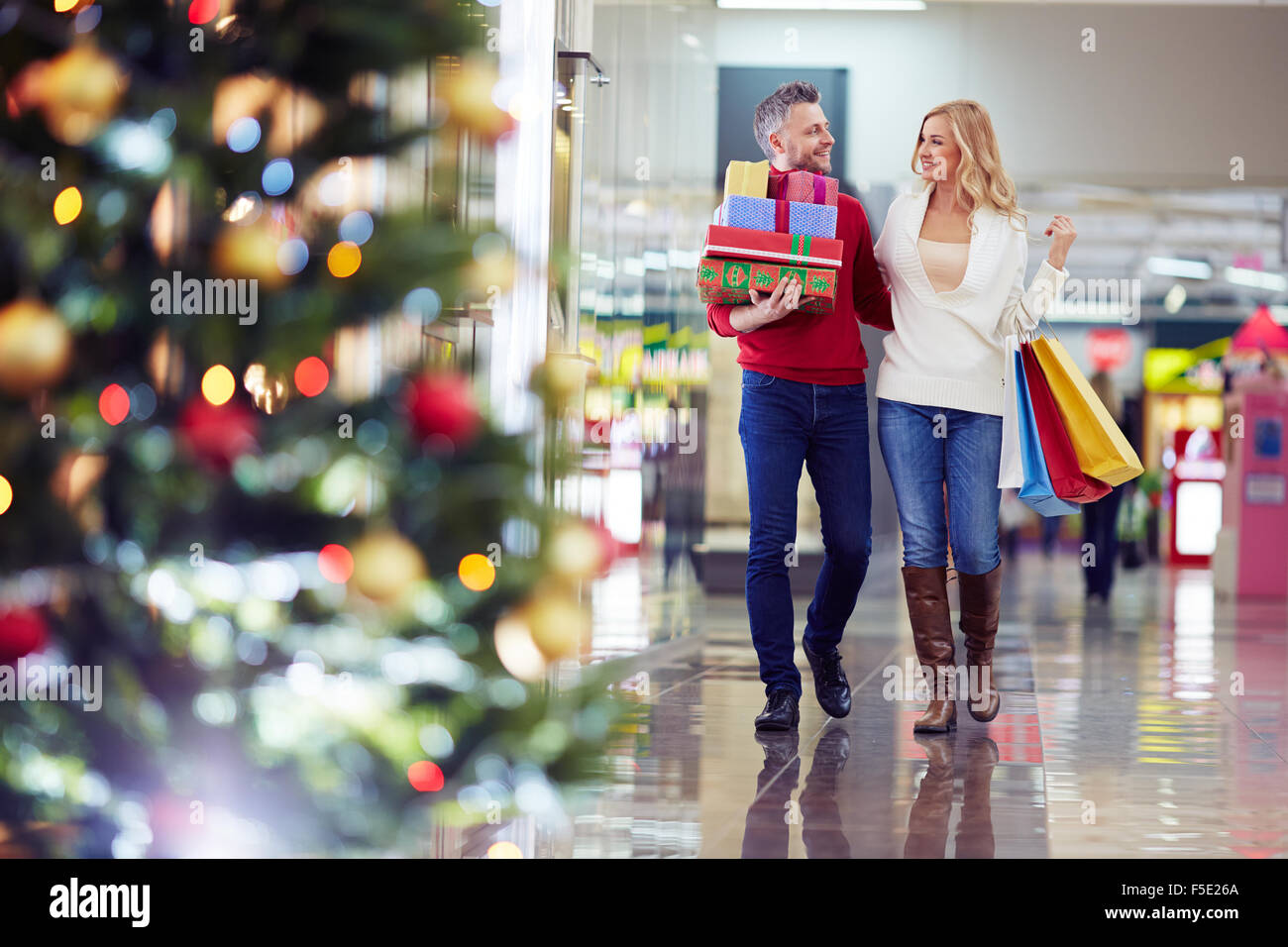 Affectionate couple buying Christmas presents in the mall - Stock Image