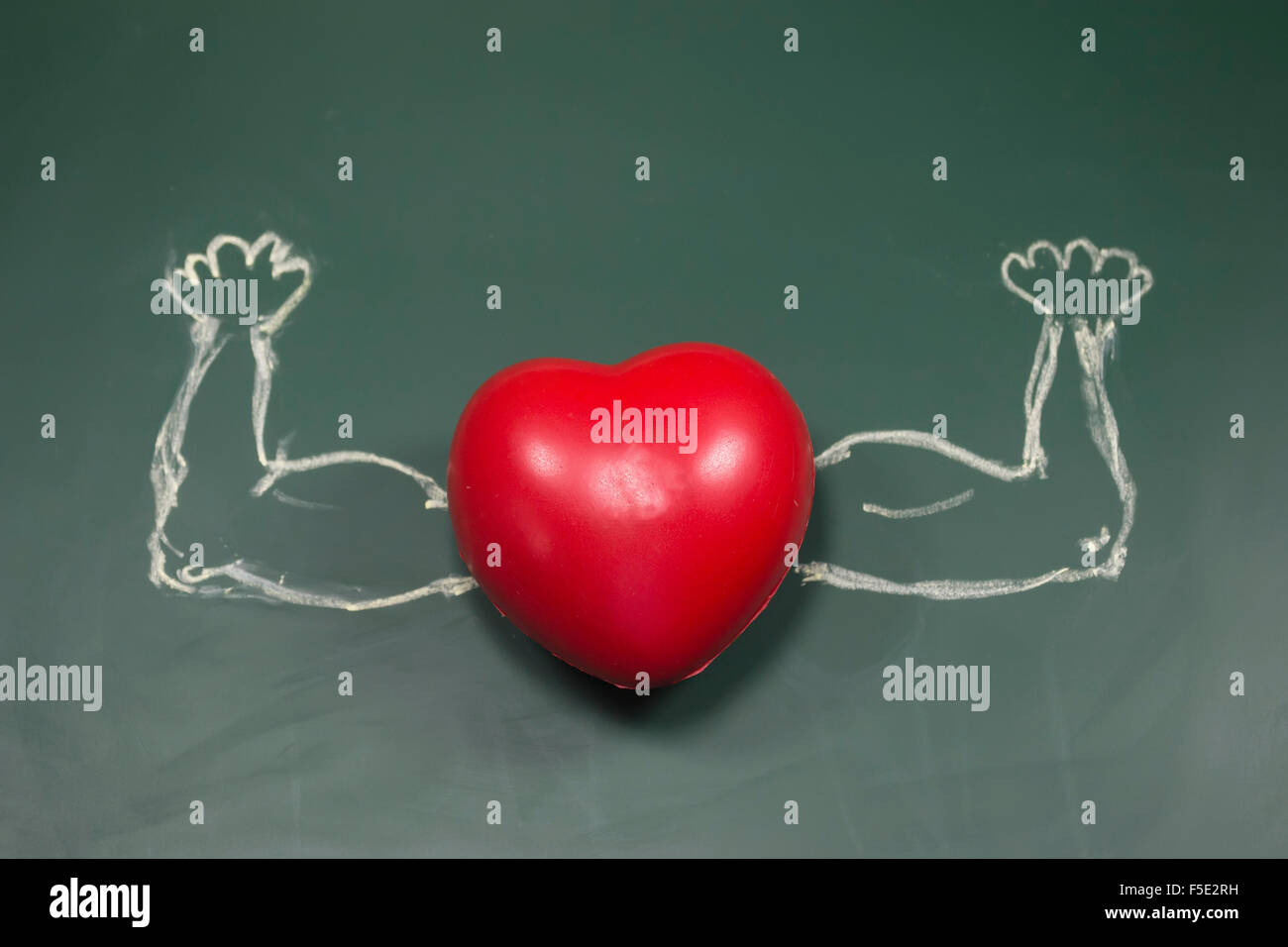 Red foam shape heart with muscle hands drawn chalk attached to it on green board - Stock Image