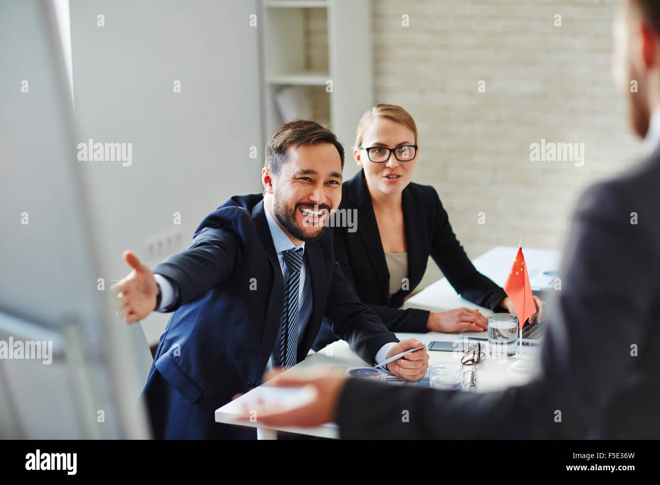 Business people welcoming and registrating foreign partners before conference Stock Photo