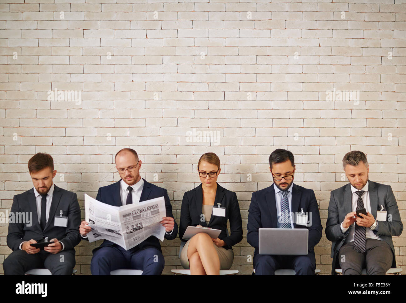 Well-dressed business people waiting for their turn to interview - Stock Image