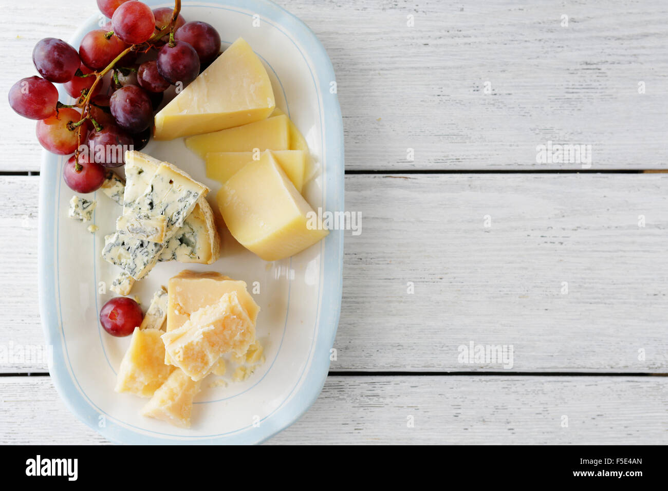 cheeses and red grapes on plate, planks food background - Stock Image