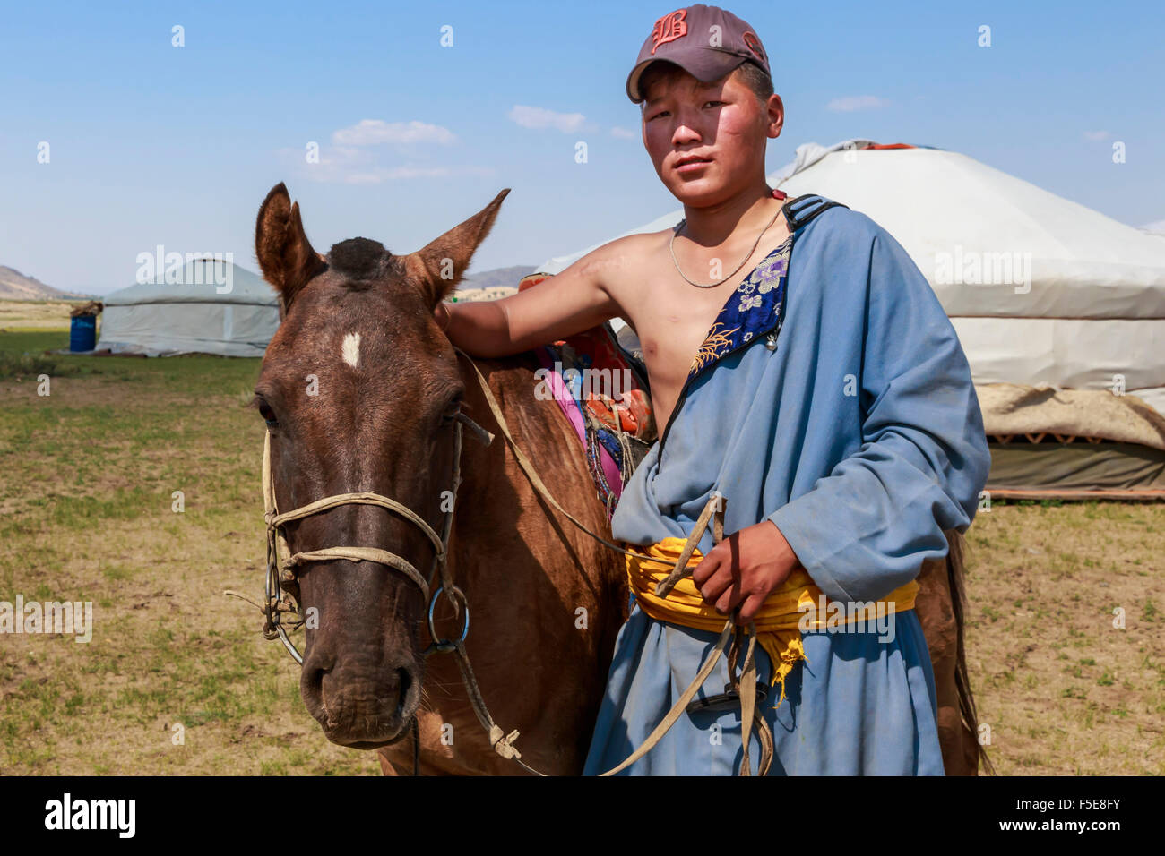Portrait of nomad in deel with his horse, Nomad gers, Khogno Khan Uul Nature Reserve, Gurvanbulag, Bulgan, Northern - Stock Image