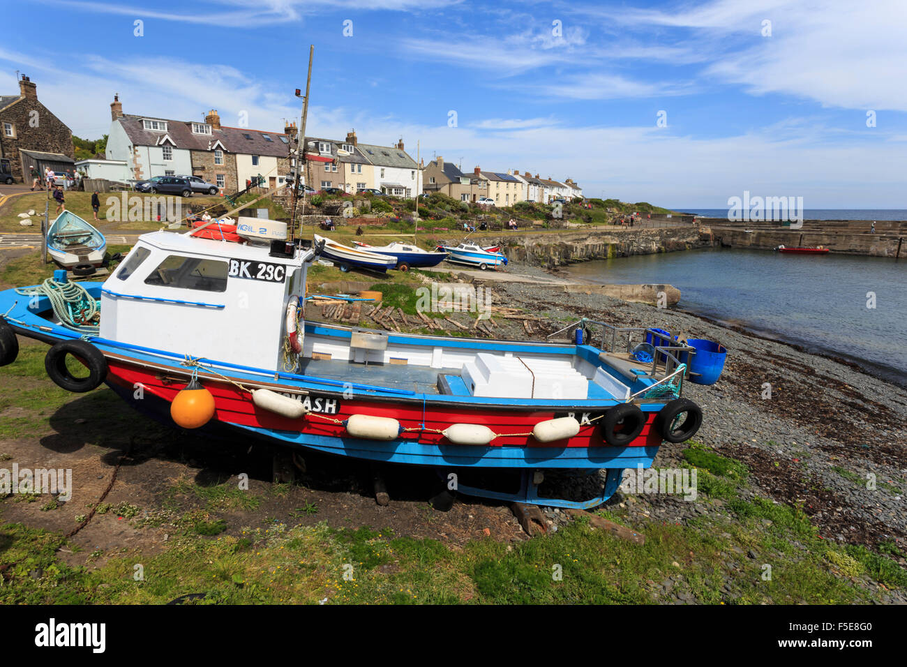 Boats on harbour foreshore at low tide on a sunny summer day, Craster, Northumberland, England, United Kingdom, - Stock Image