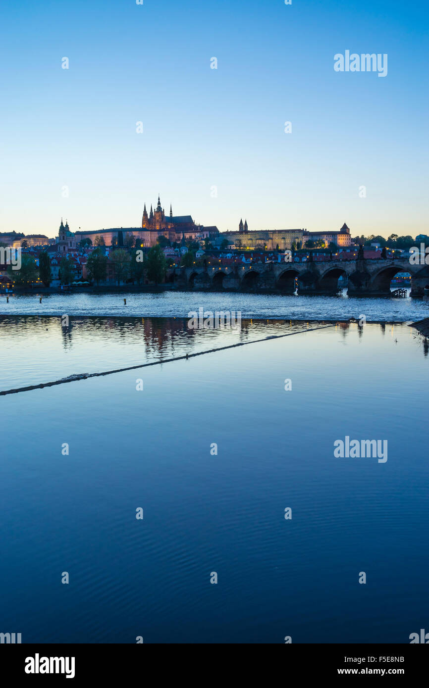 View of Charles Bridge, the Castle District and St. Vitus's Cathedral across the Vltava River at sunset, Prague, - Stock Image