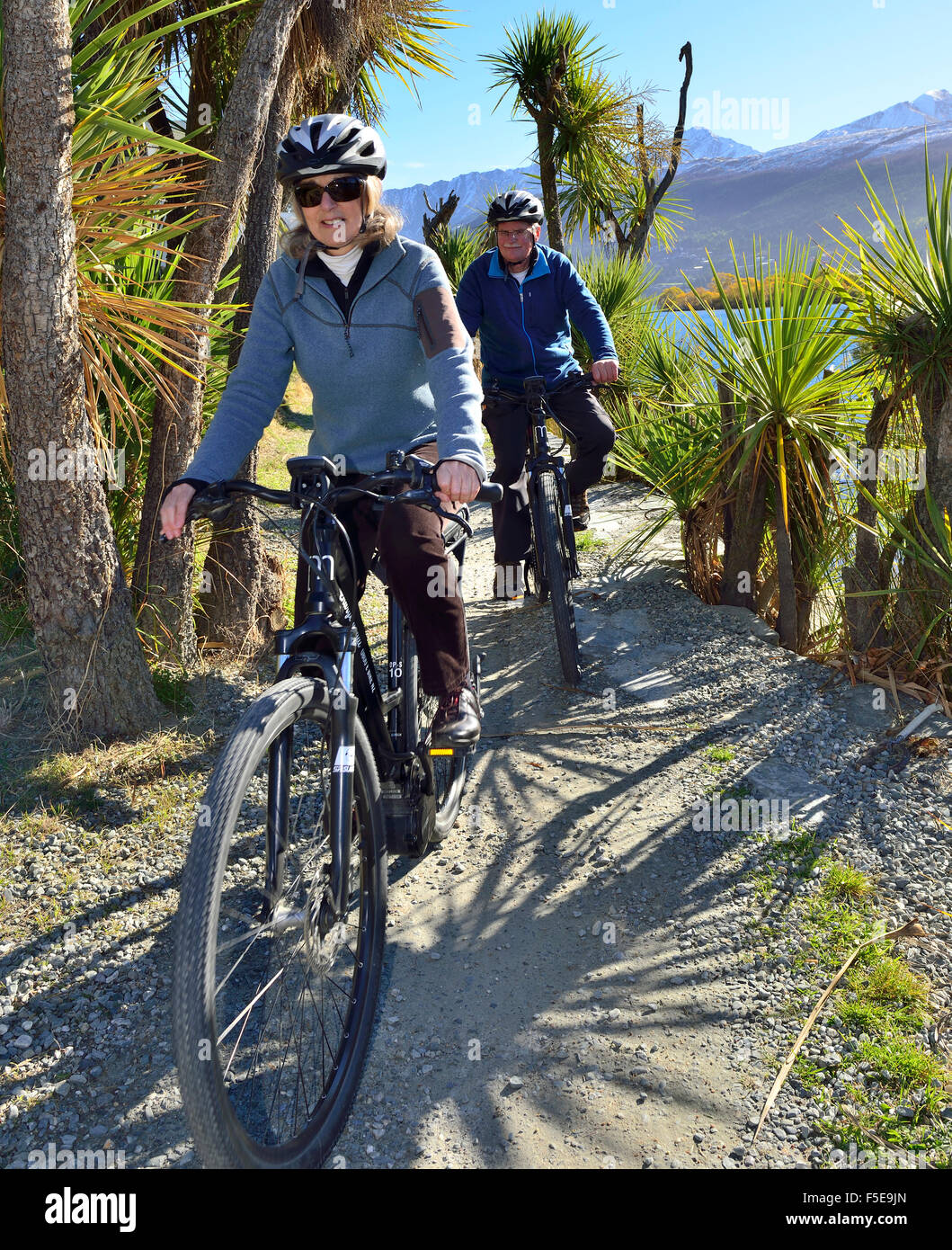 Woman and man cyclist on an electric bike,E-Bike, on the shores of  Lake Wanaka, Frankton, Queenstown, South Island, - Stock Image