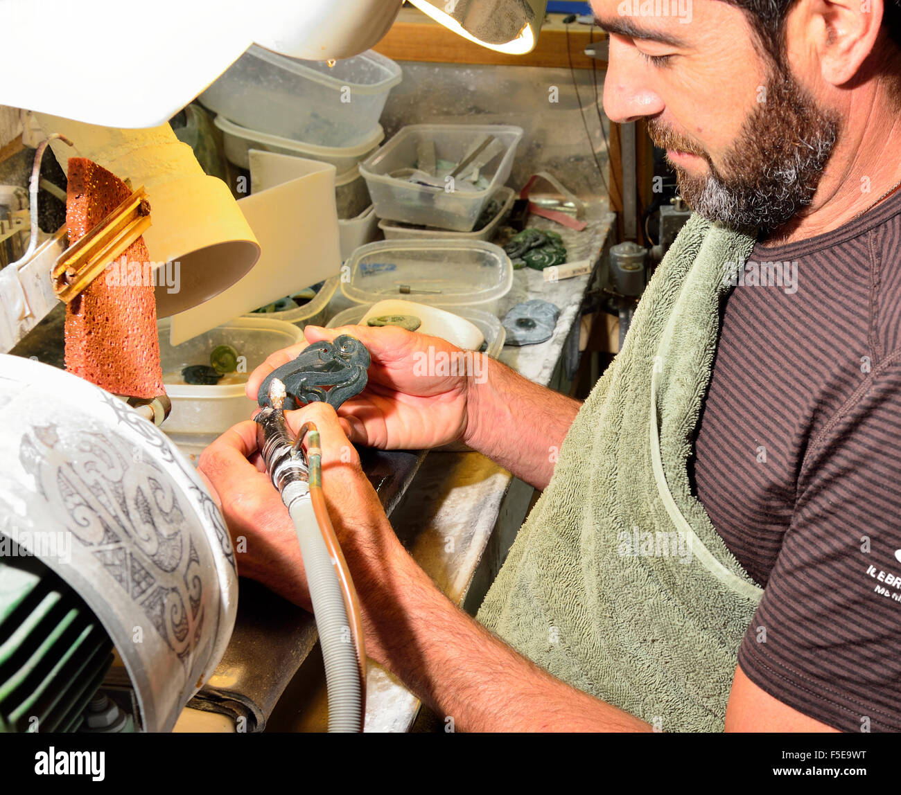 Garth Wilson in his studio carving Jade which was found in the local rivers and mountains into Maori jewellery and - Stock Image