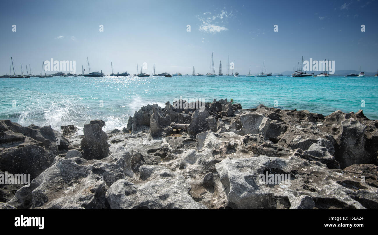 Jagged rocks with sailboats idling in the azure waters of Formentera, Balearic Islands, Spain, Mediterranean, Europe - Stock Image