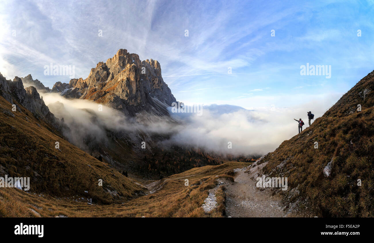 Hikers admire the peaks of Forcella De Furcia at sunrise, Funes Valley, South Tyrol, Dolomites, Italy, Europe - Stock Image