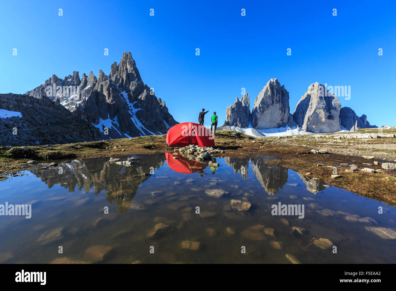 Hikers camped for the night admire the Three Peaks of Lavaredo on awakening, Sesto, Dolomites, Trentino-Alto Adige, - Stock Image