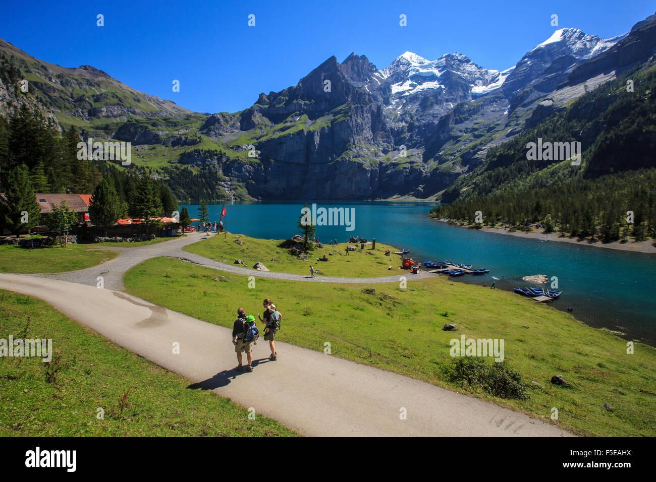 Hikers around Lake Oeschinensee, Bernese Oberland, Kandersteg, Canton of Bern, Switzerland, Europe - Stock Image