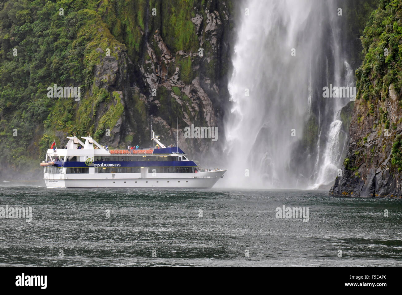 Tour boat near the Stirling waterfall, Milford sound, Fiordland National Park, New Zealand - Stock Image