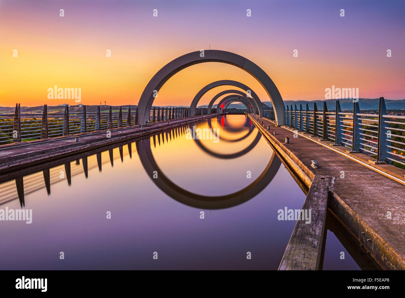 Falkirk Wheel at sunset. Falkirk Wheel is a rotating boat lift in Scotland and connects the Forth and Clyde Canal - Stock Image