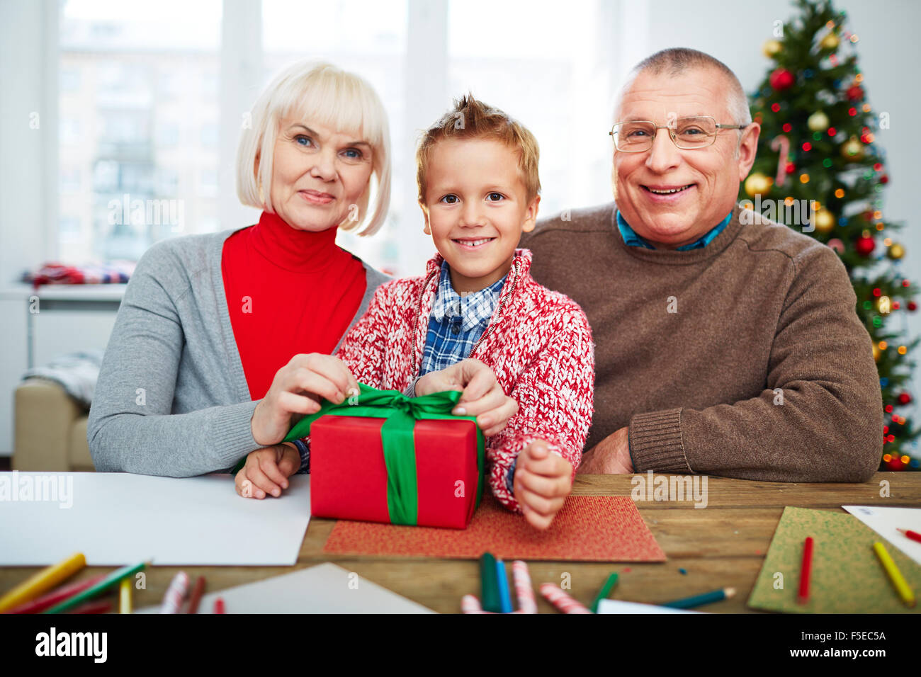 Grandparents and their grandson with giftbox looking at camera on xmas eve - Stock Image