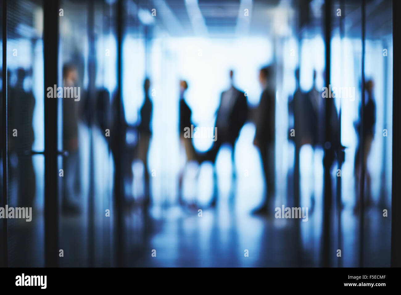 Blurred silhouettes of business people interacting in aisle of office center - Stock Image