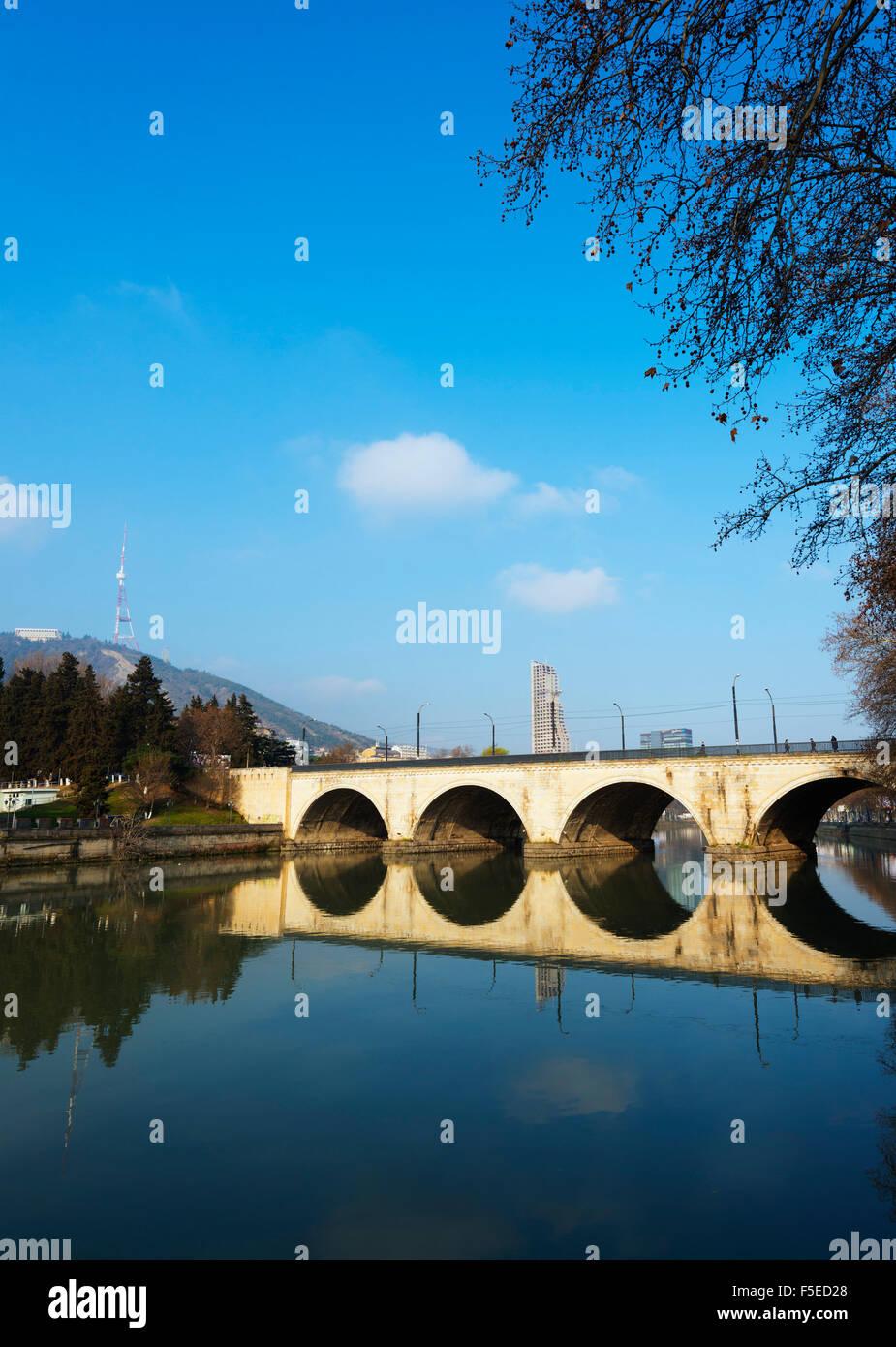 Arched bridge reflecting in Mtkvari River, Tbilisi, Georgia, Caucasus, Central Asia, Asia - Stock Image