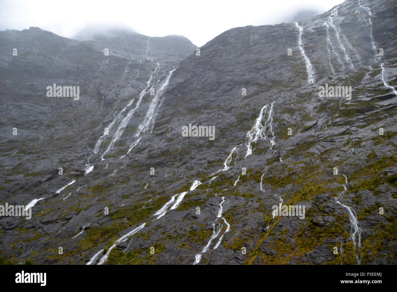 Glacier waterfalls on the road to Milford Sound, Fiordland National Park, South Island, New Zealand - Stock Image