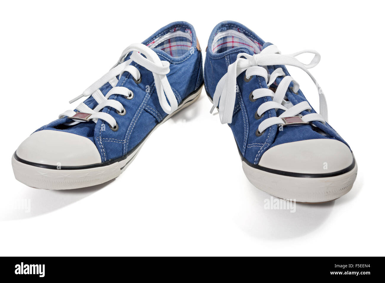 Pair of blue canvas sneakers isolated on white background - Stock Image