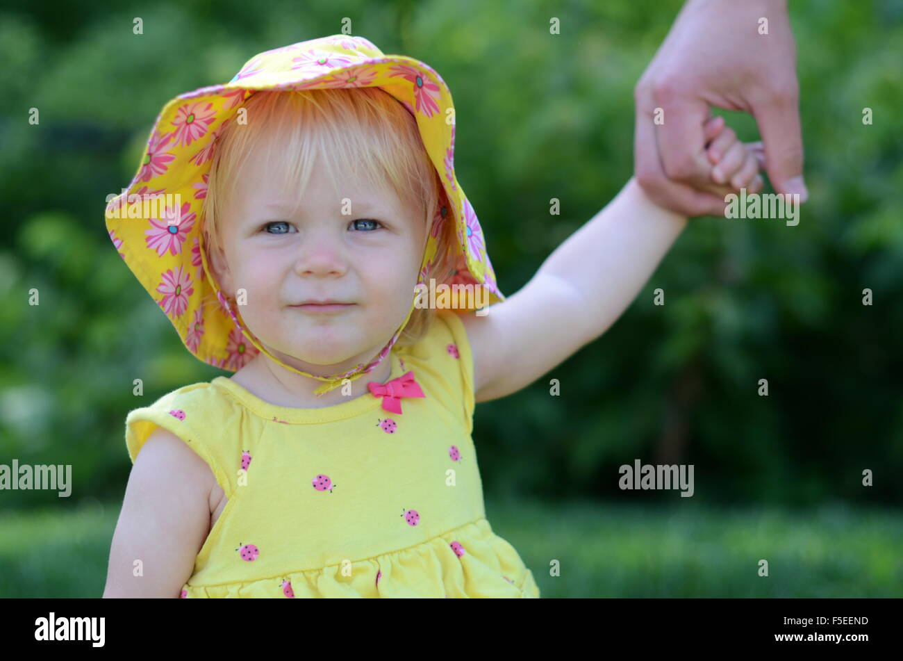 Baby girl holding her father's hand - Stock Image