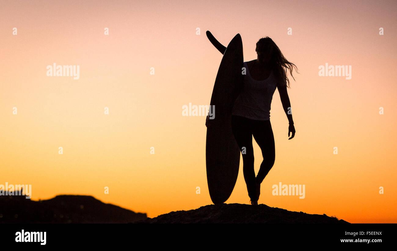 Silhouette of a woman carrying surfboard, Malibu, California, USA - Stock Image