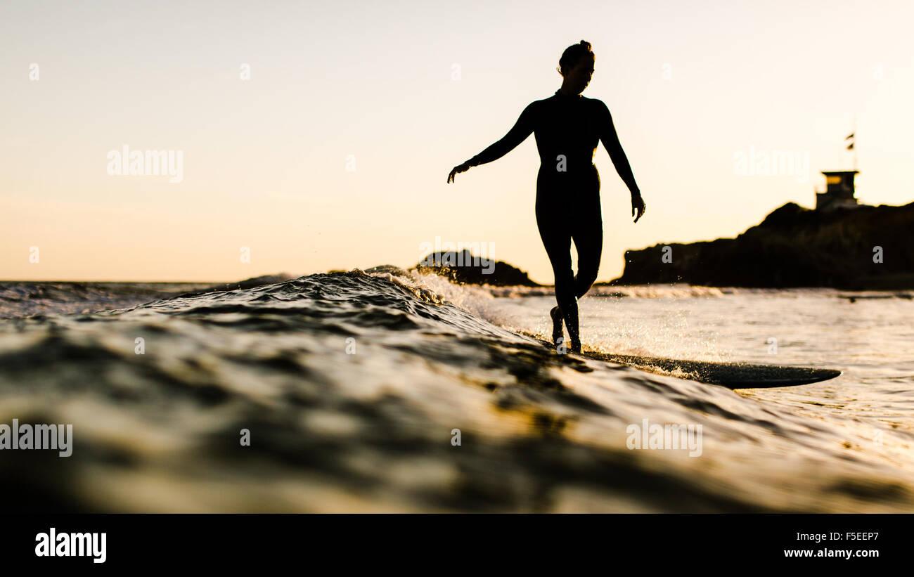 Silhouette of a woman surfing, Malibu, California, USA - Stock Image